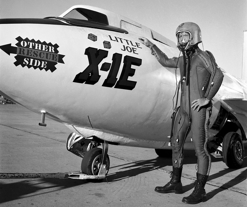 "Joe Walker in pressure suit with X-1E Description: Joe Walker in a pressure suit beside the X-1E at the NASA High-Speed Flight Station, Edwards, California. The dice and ""Little Joe"" are prominently displayed under the cockpit area. (Little Joe is a dice players slang term for two deuces.) Walker is shown in the photo wearing an early Air Force partial pressure suit. This protected the pilot if cockpit pressure was lost above 50,000 feet. Similar suits were used in such aircraft as B-47s, B-52s, F-104s, U-2s, and the X-2 and D-558-II research aircraft. Five years later, Walker reached 354,200 feet in the X-15. Similar artwork - reading ""Little Joe the II"" - was applied for the record flight. These cases are two of the few times that research aircraft carried such nose art. UID: SPD-NIX-E-3361"